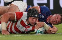 Japan's Pieter Labuschagne, left, tries to inch forward as he is tackled by a Russian player in the first half of the opener of the Rugby World Cup at Tokyo Stadium (Ajinomoto Stadium) on Sept. 20, 2019. (Mainichi/Yuki Miyatake)