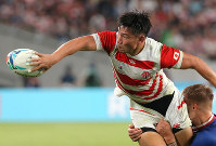 Japan's Ryoto Nakamura passes the ball while receiving a tackle by a Russian player in the first half of the opener of the Rugby World Cup at Tokyo Stadium (Ajinomoto Stadium) on Sept. 20, 2019. (Mainichi/Yuki Miyatake)