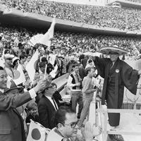 開会式で日の丸を振って応援する日本人ら。右の紋付姿は「オリンピックおじさん」こと山田直稔さん=メキシコ市で1968年(昭和43年)10月12日、松野尾章撮影