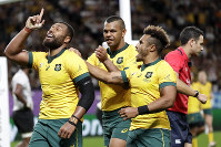 Australia's Samu Kerevi, left, celebrate with teammate Kurtley Beale and Will Genia, right, after scoring a try during the Rugby World Cup Pool D game at Sapporo Dome between Australia and Fiji in Sapporo, Japan, on Sept. 21, 2019. (AP Photo/Aaron Favila)