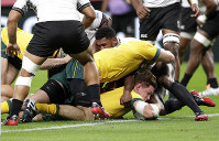 Australia's Michael Hooper, bottom, scores his team's first try during the Rugby World Cup Pool D game at Sapporo Dome between Australia and Fiji in Sapporo, Japan, on Sept. 21, 2019. (AP Photo/Aaron Favila)