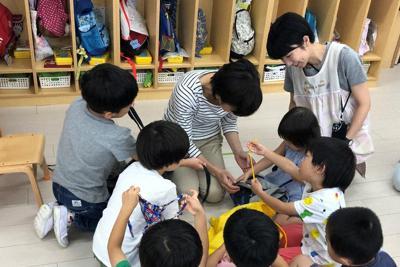 JISに適合していない服のひもなどを手に取り、どこが危ないかを話し合う園児たち=横浜市で