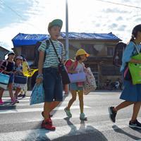 台風15号による被災後、休校が続いていた小学校が再開し、登校する児童たち。通学路わきの家屋には雨よけのブルーシートが張られている=千葉県南房総市で2019年9月17日午前7時41分、手塚耕一郎撮影