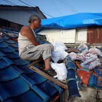 台風15号の強風で被災した屋根の上で、壊れた瓦を片付ける笹生孝之さん。「やりたくはないが、ほったらかす訳にもいかないし」と気をつけながら作業を続けた=千葉県鋸南町吉浜で2019年9月19日午後3時26分、小川昌宏撮影