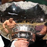 大相撲秋場所で優勝し、表彰式で受け取る内閣総理大臣杯に映り込んだ御嶽海(左)=東京・両国国技館で2019年9月22日、丸山博撮影