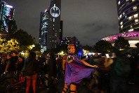 Stephanie Salgado poses with her cape during the lighting of the Bat signal commemorating Batman's 80th anniversary in Mexico City, on Saturday, Sept. 21, 2019. (AP Photo/Ginnette Riquelme)