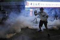 Tear gas fills the street as protesters continue to battle with police on the streets of Hong Kong on Saturday, Sept. 21, 2019. Protesters in Hong Kong threw gasoline bombs and police fired tear gas Saturday in renewed clashes over anti-government grievances (AP Photo/Kin Cheung