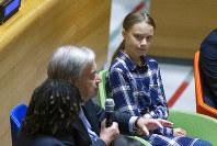Swedish environmental activist Greta Thunberg, right, listens to U.N. Secretary-General Antonio Guterres, left, during the Youth Climate Summit at United Nations headquarters, on Saturday, Sept. 21, 2019. (AP Photo/Eduardo Munoz Alvarez)