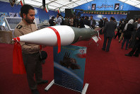 An Iranian army member looks at a missile in an exhibition in which the Revolutionary Guard also displays pieces of the American drone Global Hawk shot down by the Guard in the Strait of Hormuz in June 2019, in Tehran, Iran, on Saturday, Sept. 21, 2019. (AP Photo/Vahid Salemi)
