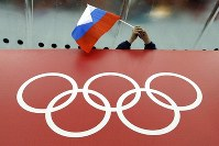 In this Feb. 18, 2014 file photo, a Russian skating fan holds the country's national flag over the Olympic rings before the men's 10,000-meter speedskating race at Adler Arena Skating Center during the Winter Olympics in Sochi, Russia. (AP Photo/David J. Phillip)