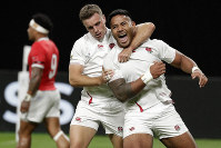 England's Manu Tuilagi, right, is congratulated by teammate George Ford after scoring his second try during the Rugby World Cup Pool C game at Sapporo Dome between England and Tonga in Sapporo, Japan, on Sept. 22, 2019. (AP Photo/Aaron Favila)
