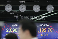 A currency trader watches his computer monitors near screens showing the Korea Composite Stock Price Index (KOSPI), left, and the foreign exchange rate between U.S. dollar and South Korean won at the foreign exchange dealing room in Seoul, South Korea, on Sept. 23, 2019. (AP Photo/Lee Jin-man)