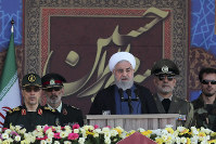 In this photo released by the official website of the office of the Iranian Presidency, President Hassan Rouhani speaks at a military parade marking 39th anniversary of outset of Iran-Iraq war, in front of the shrine of the late revolutionary founder Ayatollah Khomeini, just outside Tehran, Iran, on Sept. 22, 2019. (Iranian Presidency Office via AP)