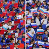 【ロシア―サモア】観客席でサモア国歌を歌う熊谷市内の中学生(左)、ロシア国家を歌う中学生ら=埼玉・熊谷ラグビー場で2019年9月24日、長谷川直亮撮影
