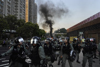 Riot police march past a burning barricade during a protest in Hong Kong, on Sept. 22, 2019. (AP Photo/Vincent Yu)