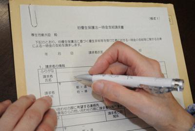 一時金支給の書類に名前を書こうとする女性=山形県鶴岡市で