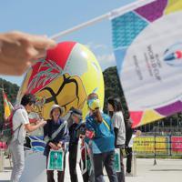 試合観戦前、会場をバックに記念撮影をする人たち=岩手県釜石市で2019年9月25日午前10時59分、和田大典撮影
