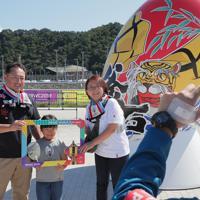 試合観戦前、会場をバックに記念撮影をする家族連れ=岩手県釜石市で2019年9月25日午前10時40分、和田大典撮影