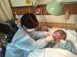 入院している父親の口のケアをする山下ゆかりさん(左)=山下さん提供