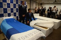 Olympic village general manager Takashi Kitajima, left, and airweave inc. head Motokuni Takaoka are seen demonstrating the cardboard beds set for use in the Athletes' Village during the 2020 Games, on Sept, 24, 2019. (Mainichi/Ryo Yanagisawa)