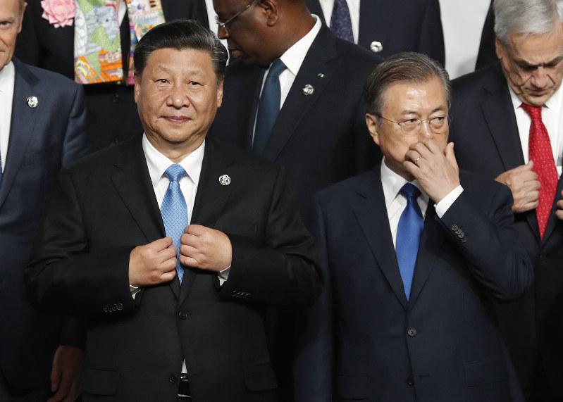 中国の習近平国家主席(左)の横に立つ韓国の文在寅大統領(右)=大阪で開催された今年6月の主要20カ国・地域(G20)首脳会議で(Bloomberg)