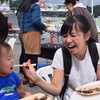 熱々のサンマをおいしそうに食べる佐藤秋生さん家族=岩手県宮古市魚市場で