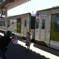 JR石巻線全線開通80周年を記念しラッピングされた列車の前で記念撮影する女の子=宮城県石巻市で