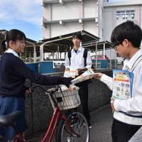 自転車で通学する生徒にチラシを配る野球部員(右)=新潟市東区の新潟東高校で