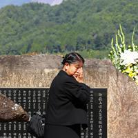 御嶽山(奥)の噴火から5年、慰霊碑の前で犠牲になった娘の由紀さんを思い、涙を流す丹羽真由美さん=長野県王滝村で2019年9月27日午前10時19分、佐々木順一撮影