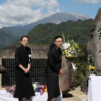 御嶽山(奥)の噴火から5年となり、夫の保男さんを亡くした伊藤ひろ美さん(左)らが慰霊碑の前で手を合わせた=長野県王滝村で2019年9月27日午前10時18分、佐々木順一撮影