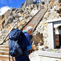噴火から5年を迎えた御嶽山に登り、山頂の慰霊碑に手を合わせる男性=長野県木曽町で2019年9月27日午前10時26分、島袋太輔撮影