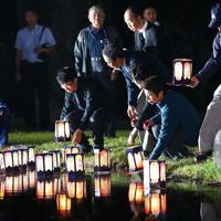 御嶽山の噴火から5年を迎え、公園で灯籠を浮かべる遺族ら=長野県木曽町で2019年9月27日午後6時6分、佐々木順一撮影
