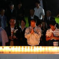 御嶽山の噴火から5年を迎え、公園で献花して手を合わせる遺族ら=長野県木曽町で2019年9月27日午後6時14分、佐々木順一撮影