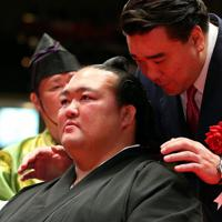 断髪式で、元横綱・日馬富士(右)にはさみを入れられ、涙する元横綱・稀勢の里の荒磯親方=東京・両国国技館で2019年9月29日、小川昌宏撮影