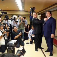 断髪式を終え、大勢の報道陣に囲まれながらスーツ姿で笑顔を見せる元横綱・稀勢の里の荒磯親方(右端)=東京・両国国技館で2019年9月29日、小川昌宏撮影