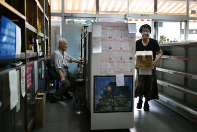 商品が少なくなった店内でレジカウンターの椅子に座る植田義昭さん(左)と片付けをする妻好子さん=大阪府八尾市で2019年9月27日午後4時24分、小出洋平撮影