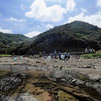 漂着したごみを集めるボランティアの学生たち。海岸には美しい磯が広がっている=津村豊和