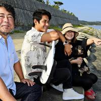 小さな頃から遊んだ海岸を見つめる田中さん(中央)。手前は父の大蔵さん、奥は母の由美子さん。試合の後は今でもサーフィンの話をする=矢頭智剛