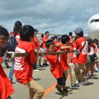 ジェット機を動かそうと、一生懸命に綱を引っ張る子どもたち=成田空港で