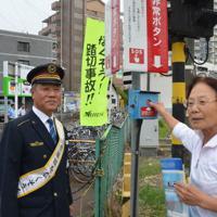 非常ボタンを押し電車に危険を知らせてほしいと、通りかかった人に呼びかける沢村忠駅長(左)=愛知県岩倉市の踏切で