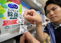 An employee shows a price tag that reflects the new 10% consumption tax, top, and an old one for 8% at an outlet of the major convenience store chain Lawson in Tokyo's Shinagawa Ward just after the consumption tax increase came into effect on Oct. 1, 2019. (Mainichi/Naotsune Umemura)