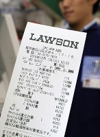 A receipt for items including food, to which the reduced consumption tax rate of 8% is applied, is seen at an outlet of the major convenience store chain Lawson in Tokyo's Shinagawa Ward just after the tax hike to 10% came into effect on Oct. 1, 2019. (Mainichi/Naotsune Umemura)