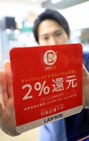 An employee places a sticker informing shoppers of a 2% time-limited reduction in the consumption tax rate for cashless payments at an outlet of the major convenience store chain Lawson in Tokyo's Shinagawa Ward just after the tax increase to 10% came into effect on Oct. 1, 2019. (Mainichi/Naotsune Umemura)