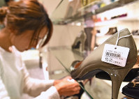 An employee is seen changing price tags on goods after closing time at the Fukuoka Tenjin outlet of the Daimaru department store in Fukuoka's Chuo Ward on Sept. 30, 2019, the day before the consumption tax increase from 8% to 10% came into effect. (Mainichi/Tomohisa Yazu)