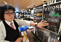 An employee changes price signs for alcohol at the Kintetsu Department Store Main Store Abeno Harukas on Sept. 30, 2019, the day before the consumption tax increase from 8% to 10% came into effect. (Mainichi/Kenji Konoha)