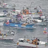 大漁旗をたてて海上を勇壮に進む漁船団=福岡県宗像市の大島沖で2019年10月1日午前9時42分、本社ヘリから矢頭智剛撮影