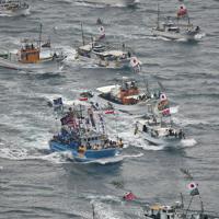白波をたてながら海上を勇壮に進む漁船団=福岡県宗像市の大島沖で2019年10月1日午前9時56分、本社ヘリから矢頭智剛撮影