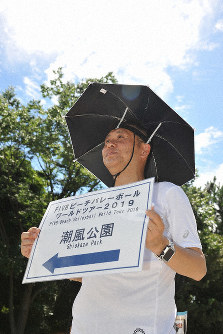 A volunteer worker whose role is to lead spectators to a test event venue is seen wearing a pilot umbrella hat at Shiokaze Park in Tokyo's Shinagawa Ward on July 26, 2019. (Mainichi/Koichi Uchida)