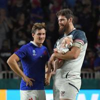 【フランス―米国】試合を終え、ピッチ上で赤ちゃんを抱いた米国のピーターソン(右)と笑顔で話すフランスのセラン=レベルファイブスタジアムで2019年10月2日、森園道子撮影