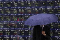 街頭の株価ボード前の通行人(Bloomberg)